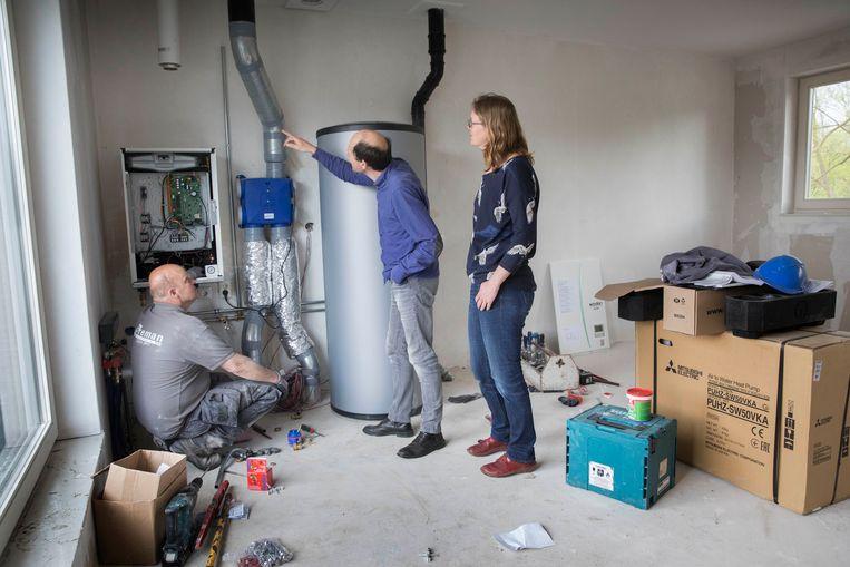 Een installateur is bezig met het aansluiten van een pompinstallatie voor een gasloze woning. Beeld null