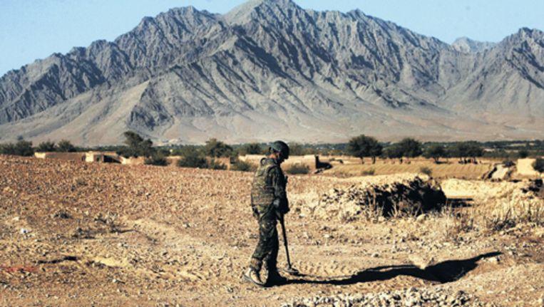 cIn de omgeving van de vooruitgeschoven Combat Outpost Tabar zoekt een militair naar bermbommen. In deze buurt stierf gisteren een Nederlander. Foto GPD Beeld