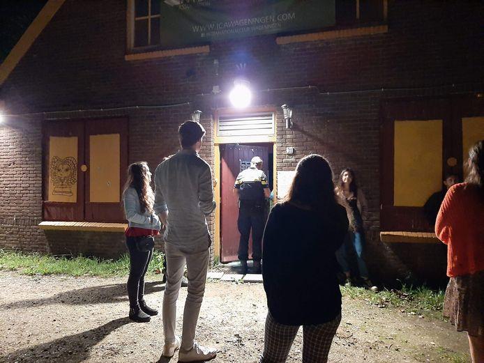 De politie voor de deur van de International Club Wageningen.