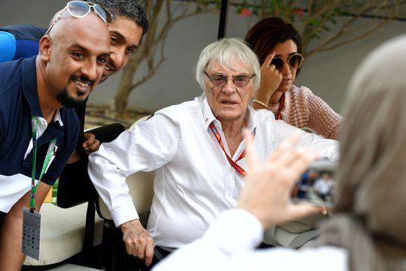 Bernie Ecclestone omgeven door fans voor een foto.