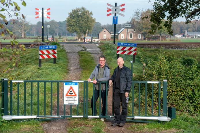 Richard Meijers (links) bij de overweg met op de achtergrond zijn huis. Zijn buurman Christiaan Henny (rechts) is niet de buurman die Meijers de gang over zijn land weigert. Hij woont aan deze kant van de spoorlijn en heeft als veiligheidsmaatregel zelf maar een hekje gemaakt.