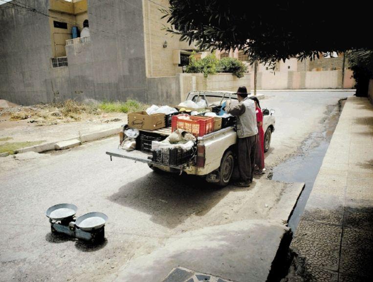Een Iraakse handelaar helpt een klant. De weegschaal is even op straat gezet. (FOTO'S EDDY VAN WESSEL) Beeld