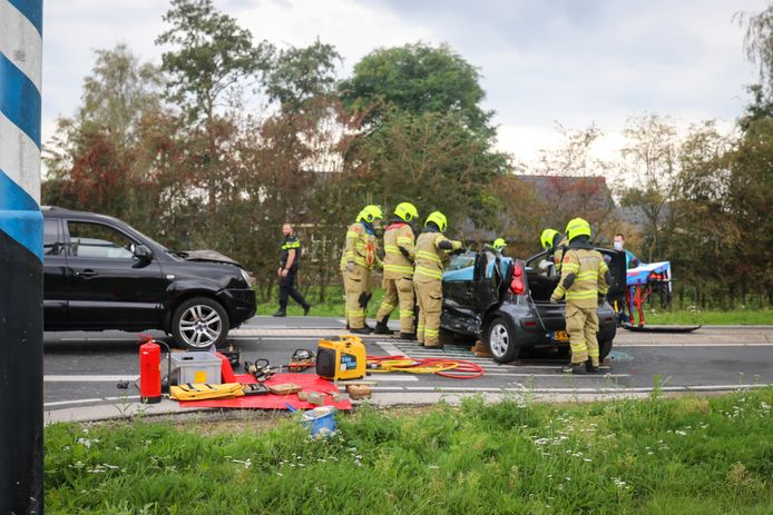 De brandweer probeert de vrouw uit haar auto te halen.