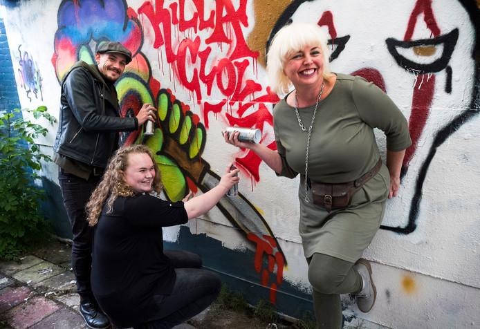 Naomi en pedagogisch medewerker Enrico spuiten graffiti. Rechts Jenneke van Wijngaarden van de Dorpsacademie.
