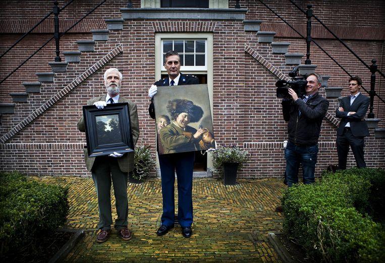In 2011 en 1988 werd de 'Twee lachende jongens' eveneens gestolen, directeur van het museum Het Hofje van Mevrouw van Aerden, Maarten van Kruyswijk (L) en districtchef Alblasserwaard, Bart Willemsen tonen de teruggevonden schilderijen.  Beeld ANP