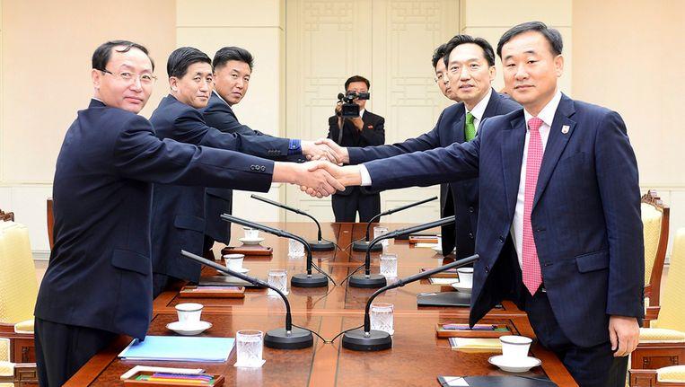 Vertegenwoordigers van Noord- en Zuid-Korea schudden elkaar de hand. Beeld EPA