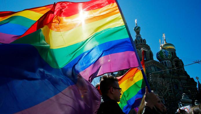 Een homorechtenactivist draagt een regenboogvlag voor het Kremlin.