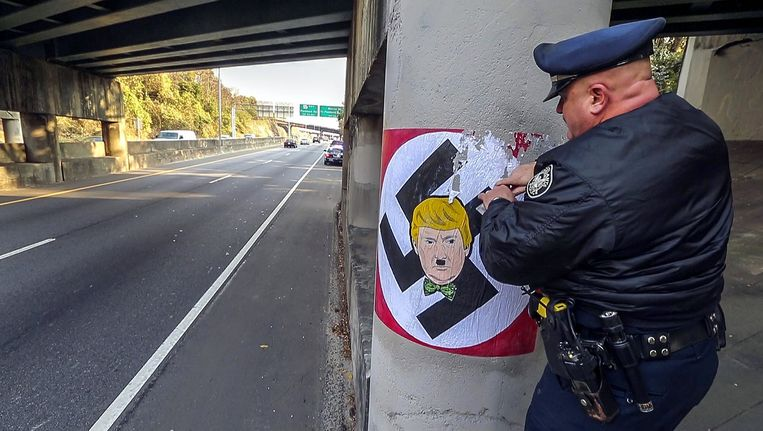 Een agent krabt een schildering van een hakenkruis met het hoofd van Donald Trump voorzien van een hitlersnorretje van een viaduct in Atlanta. Beeld epa