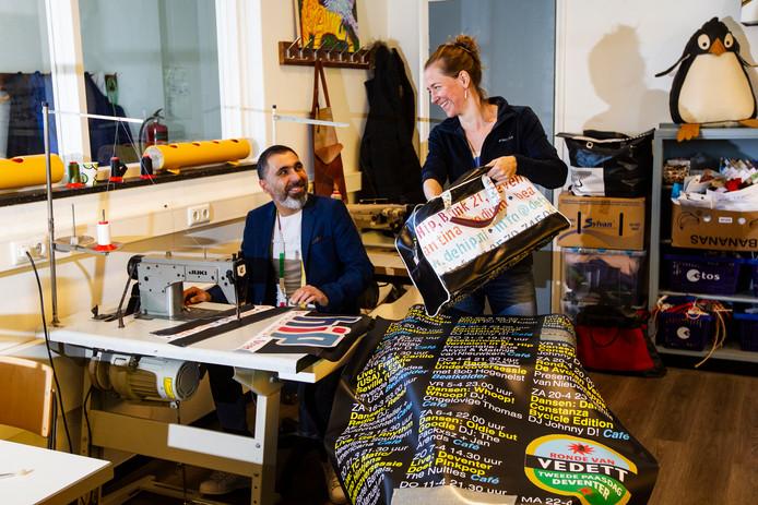 De Syrische vluchteling Jaafar Jaafar heeft met Annet Verhoeven plezier in het maken van de tassen.
