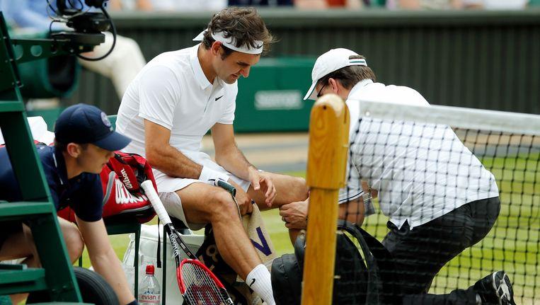 Roger Federer wordt behandeld in zijn wedstrijd tegen Milos Raonic op Wimbledon. Beeld ap