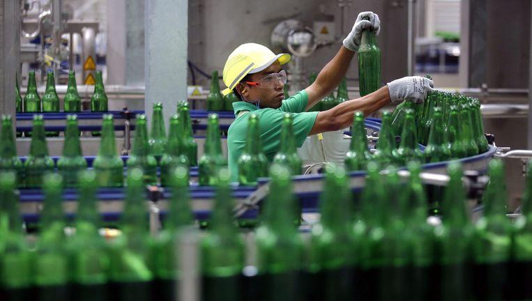 Een fabrieksmedewerker checkt lege flesjes van Regal Seven bier in de nieuwe fabriek van Heineken vlakbij Yangon, Myanmar. Beeld EPA