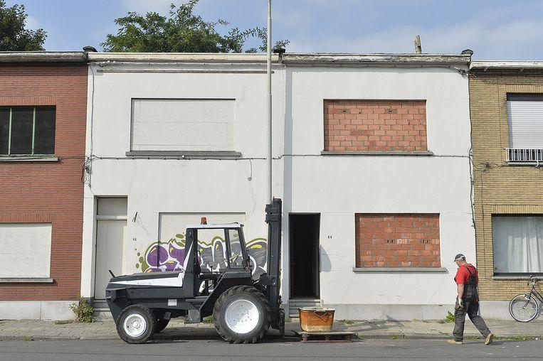 Een aannemer aan de slag aan het huis naast dat van Terryn. Het pand is aan de binnenkant gestript, de ramen zijn dichtgemetseld.