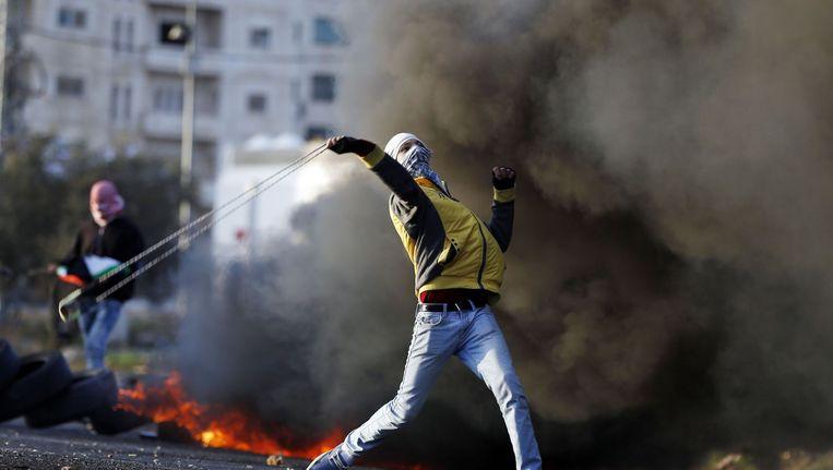 Een Palestijn gebruikt een katapultwapen tegen het Israëlische leger in de buurt van de stad Ramallah in de Westelijke Jordaanoever. Beeld afp