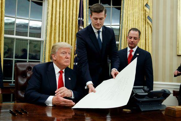 Rob Porter (m.), overhandigt Trump een document in het Witte Huis terwijl toenmalig stafchef Reince Priebus toekijkt.