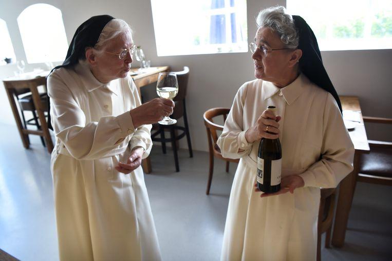 De zusters Norbertinessen proeven uit hun eerste fles wijn.  Beeld null