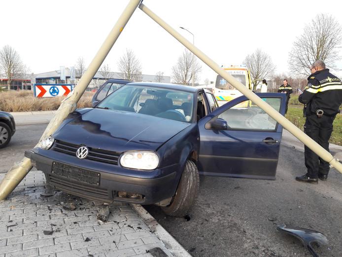 De auto en de uit de grond gerukte lantaarnpaal.