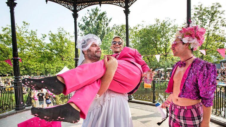 Twee geliefden vieren hun huwelijk voor een dag, een 'ambtenaar' kijkt vol bewondering toe. Beeld Guus Dubbelman / de Volkskrant