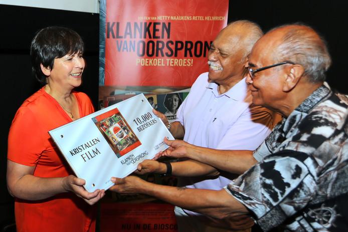Hetty Naaijkens-Retel Helmrich ontvangt de Kristallen Film uit handen van Eddy Chatelin en Hans Bax (r).
