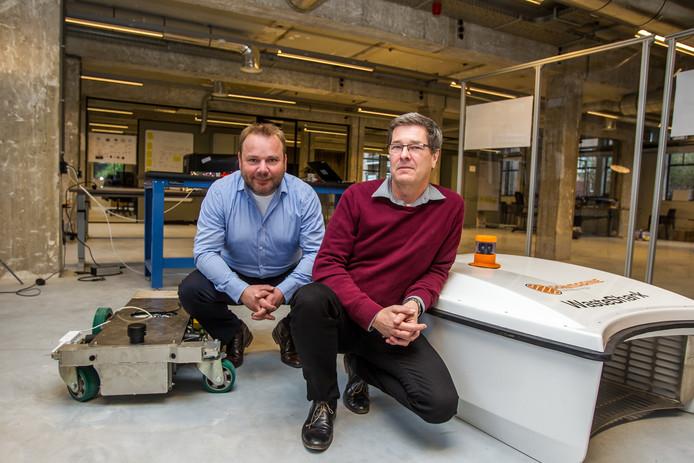 Gerrit Dijkhoff (links) en Frank Sperling poseren bij de 'waste shark', een robot die wordt ontwikkeld om afval in havens te verzamelen.