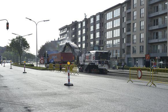 Arbeiders brengen nieuwe asfalt aan.