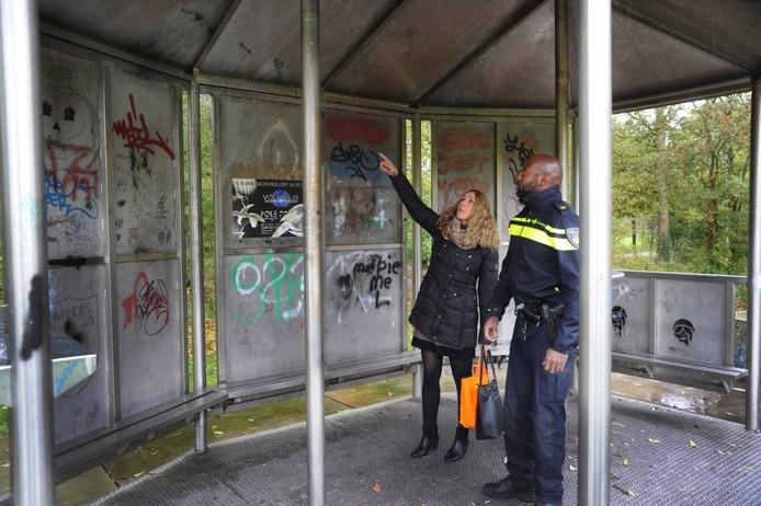 Wijkmanager Rianne van Iwaarden en wijkagent Freddy den Heijer nemen een kijkje bij de graffiti op een kiosk op het Meiveld.