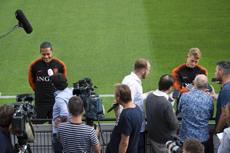 Een lachende Virgil van Dijk (links) naast een ernstige Matthijs De Ligt in aanloop naar de EK-kwalificatiewedstrijd tegen Duitsland.