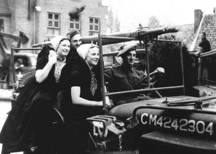 Twee vrouwen uit Zeeland rijden mee op een jeep van de geallieerden tijdens de intocht van de bevrijding van Nederland. Foto: ANP