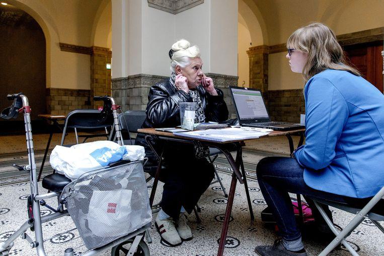Een vrijwilliger (rechts) helpt een belastingplichtige met de aangifte. Beeld anp