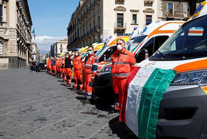 Hulpverleners in Catania houden een minuut stilte.