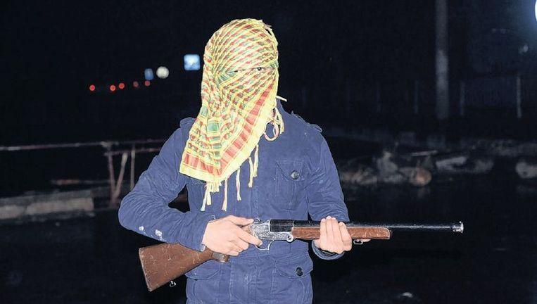 Een lid van de PKK bij een wegversperring in Cirze, in het zuidoosten van Turkije, nabij de Syrische grens. Beeld anp