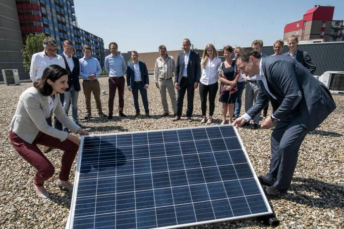 Wethouder Haga en head business innovations Wouter van de Braak van Wereldhave leggen het eerste zonnnepaneel op het dak van winkelcentrum Kronenburg.