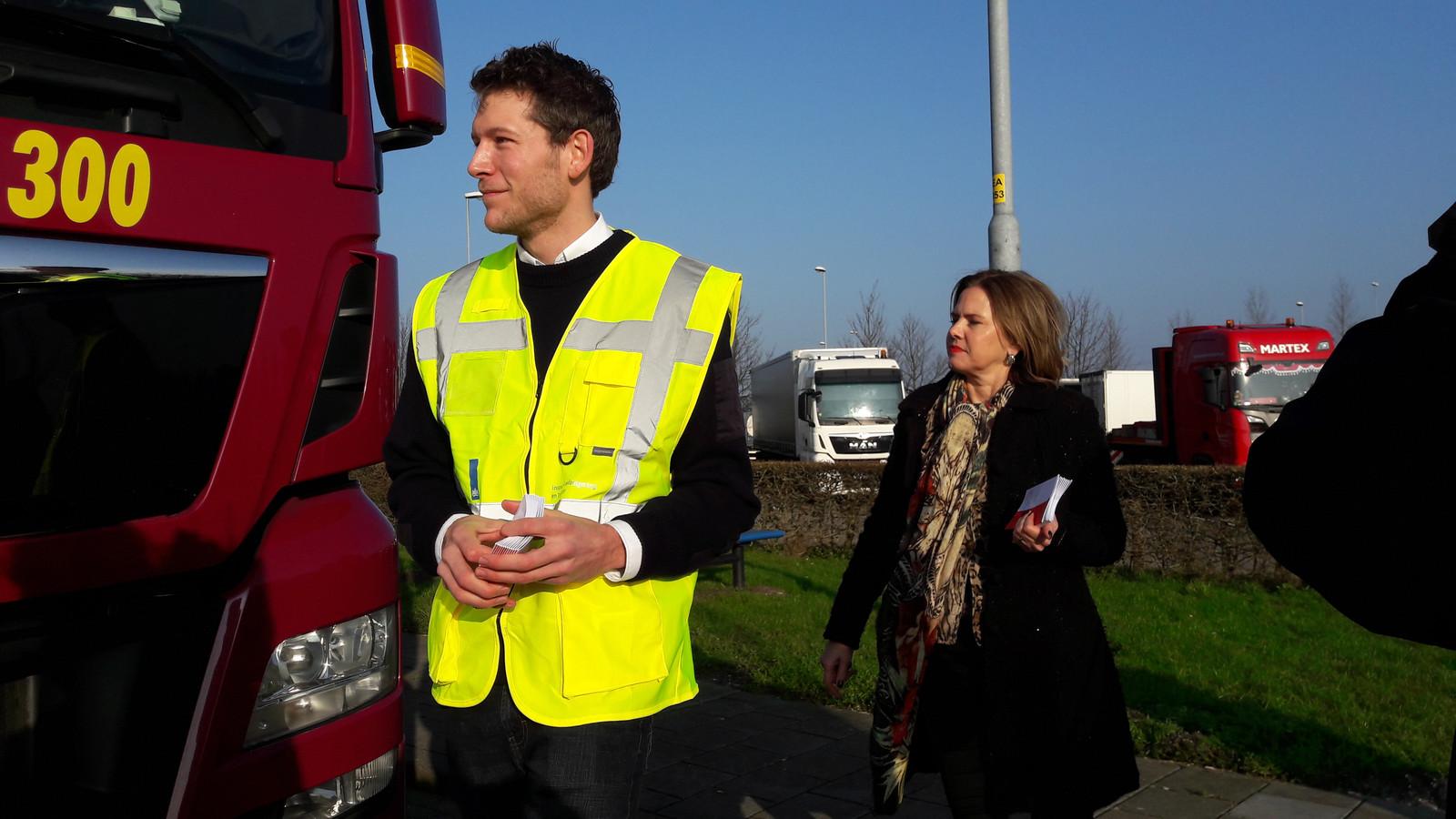 Minister van Infrastructuur en Waterstaat Cora van Nieuwenhuizen deelt met een inspecteur Leefomgeving en Transport folders uit op parkeerplaats Den Hoek langs de A16 ter hoogte van Zevenbergen.