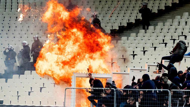 Voorafgaand aan de Champions Leaguewedstrijd van AEK Athene en Ajax waren er rellen op de tribune tussen fans van beide teams. Er werd ook een molotovcocktail naar de Ajax-fans gegooid. Beeld anp