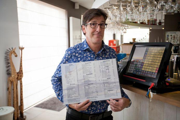 Zaakvoerder Dirk Hillewaere van restaurant Sint-Nikolaas met de menukaart, waarop duidelijk staat dat koperen centen niet aanvaard worden.