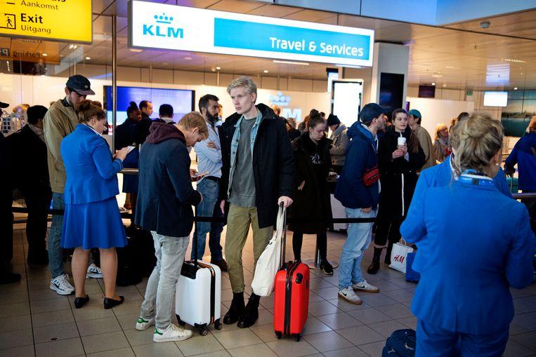 Drukte in de vertrekhal bij de informatiebalie van KLM op Schiphol. Beeld ANP
