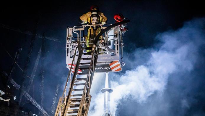 Een brandweerman tijdens het blussen van de brand in de Sint Urbanuskerk.