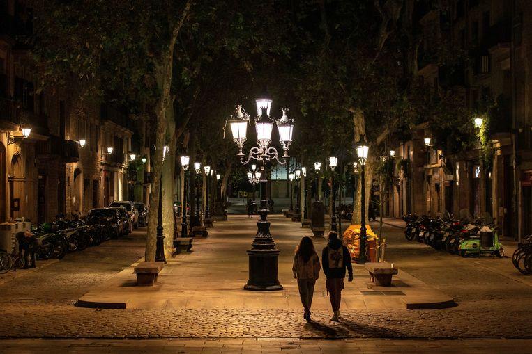 Mensen wandelen over de lege Passeig del Born tijdens de avondklok in Barcelona. Premier Sanchez kondigde zondag de noodtoestand af in Spanje, om de verspreiding van het coronavirus tegen te gaan.  Beeld EPA