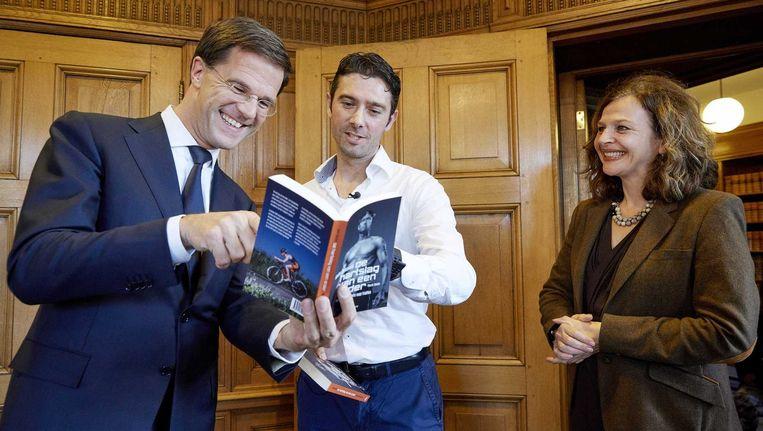Triatleet Wouter Duinisveld bekijkt een exemplaar van zijn boek De Hartslag van een Ander met premier Rutte (l) en minister Schippers (r) van Volksgezondheid, Welzijn en Sport in het kader van de Donorweek. Hij onderging in 2006 een harttransplantatie. Beeld anp
