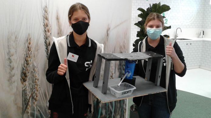 Simone van der Stap (l) en Manja van Bokhoven presenteren hun omgekeerde drempel, ook een manier om water op te vangen.