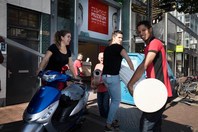 Verhuizing van MuZIEum. Verhuizers en vrijwilligers gaan met inventaris het het voormalige Tilderspand in de Ziekerstraat binnen.
