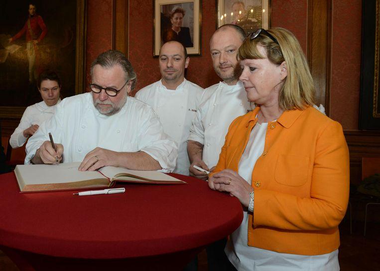 Topchef Geert Van Hecke ondertekent het guldenboek. Collega's Karen Keygnaert, Alex Hanbuckers en Dominique Persoone en schepen Hilde Decleer kijken toe.