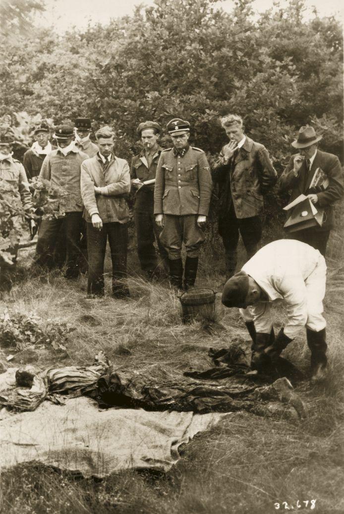 LEUSDEN, 27 JUNI 1945 In kamp Amersfoort zijn tijdens de oorlog naar schatting 350 gevangenen geëxecuteerd. Kort na de bevrijding worden hun lichamen opgegraven om te worden herbegraven. Er zijn massagraven op verschillende plaatsen: vlak bij de executieplaats, in de omgeving van het kamp en op de Leusderhei. Commandant Karl Berg (in uniform) is uit zijn cel gehaald om aan te wijzen waar de stoffelijke overschotten te vinden zijn. Links staat het personeel van de Amersfoortse GG&GD en Gemeentereiniging, dat de eerste opgravingen uitvoerde. Ook Gerrit Kleinveld, voormalig gevangene van Kamp Amersfoort, is aanwezig. De drie heren rechts van Berg zijn onbekend, maar mogelijk is de man met de aktetas de Amersfoortse arts dr. Dekker, die bij de eerste opgravingen was betrokken. Berg is nog altijd in het uniform dat hij bij zijn arrestatie droeg. Als kampcommandant had hij zich op zeer wrede en sadistische wijze gemanifesteerd. Later is hij in Nederland berecht en ter dood gebracht.