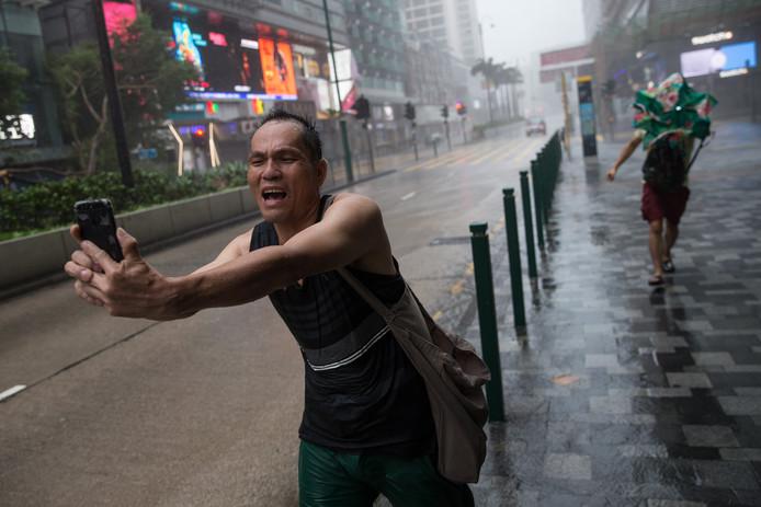 Een man in Hong Kong maakt een selfie in de storm.