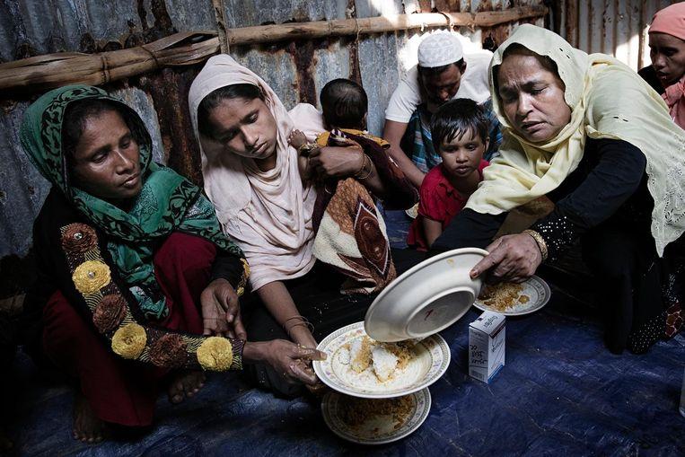 In een schuur krijgt de groep te eten van Bengalezen. Jaheda Kahtun deelt uit. Beeld Daniel Rosenthal / de Volkskrant