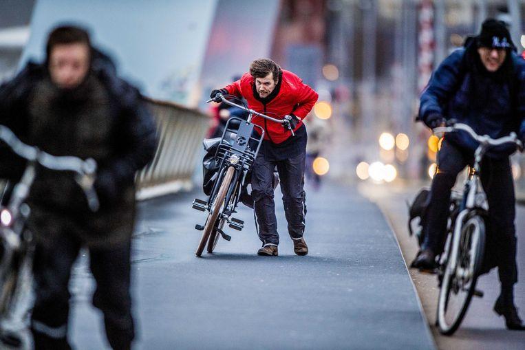 Een fietser trapt tegen de westerstorm op de Erasmusbrug in Rotterdam.