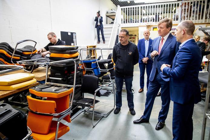 Koning Willem-Alexander krijgt uitleg van directeur Henry Joustra (rechts) en bedrijfsleider Frank Verheul over het herstofferen van stoelen.