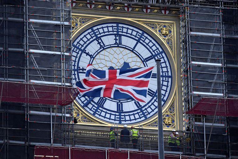 Een fier wapperende Union Jack voor een van de vernieuwde wijzerplaten van de Big Ben, die nog altijd in de steigers staat.