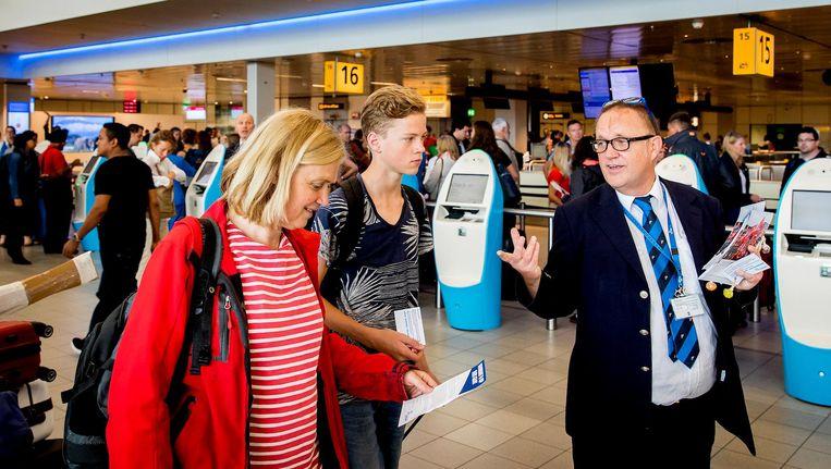 Werknemers van KLM delen flyers uit aan reizigers op Schiphol Beeld anp