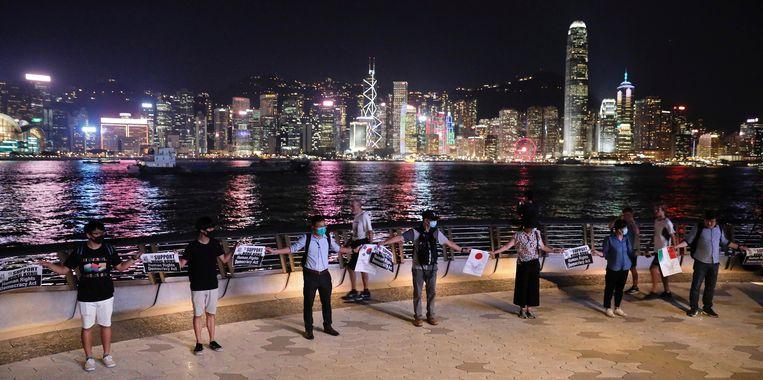 Demonstranten in Hongkong houden elkaars handen vast om een 40 kilometer lange menselijke ketting te vormen uit protest. Het is vandaag precies 30 jaar geleden dat demonstranten in de Baltische staten eenzelfde keten vormden om hun onafhankelijkheid te eisen van de Sovjet-Unie. Deze 'Baltische Weg' was 600 kilometer lang en bestond uit 2 miljoen mensen.  Beeld null
