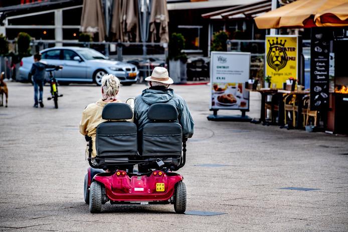 Bejaarden in een scootmobiel voor twee personen
